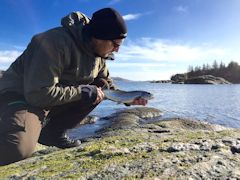Ryan Marchese guide holding trout at edge of lake kneeling on one knee